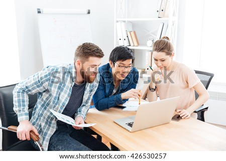 Three focused young businesspeople working with laptop in office together - stock photo