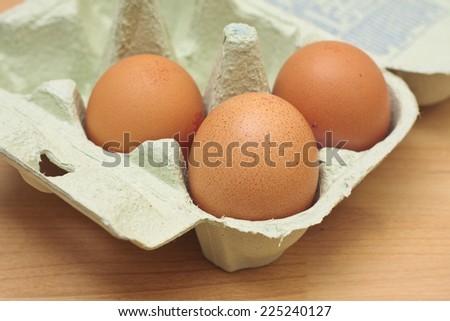 Three free-range chicken eggs in a green egg box - stock photo