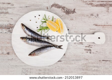 Three fresh anchovy fish on white round kitchen board on white wooden table, top view. Culinary seafood concept. Delicious healthy eating. - stock photo