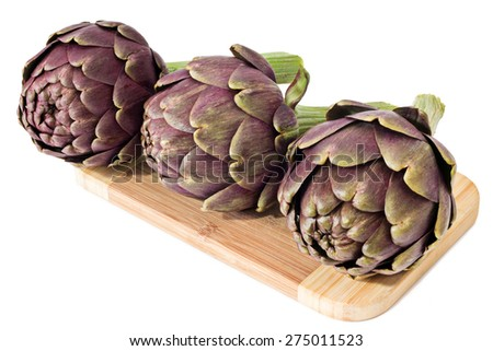 Three fresh artichokes on a cutting board - stock photo