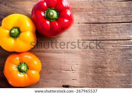 Three Fresh Bell Peppers in Red, Yellow and Orange on Top of Wooden Market Table with Copy Space for Texts. Captured in High Angle View. - stock photo
