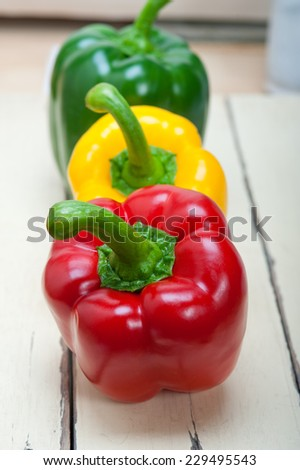 three fresh bell peppers over old wood table - stock photo