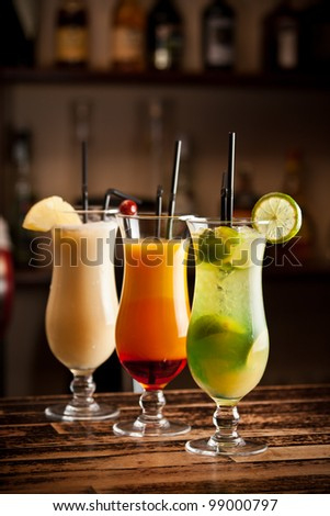 Three fresh cocktails on a bar table - stock photo