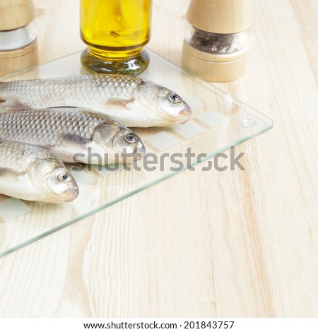 Three fresh fishes on a wooden table. - stock photo