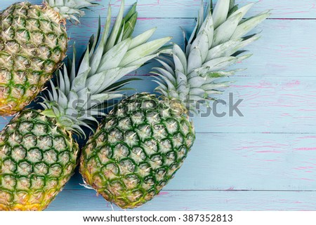 Three fresh juicy tropical pineapples with their green leaves laid out side by side on a blue table with copy space viewed from above - stock photo