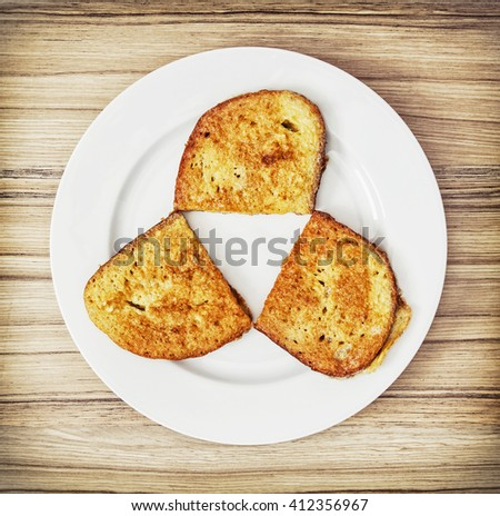 Three fried breads in the egg.  Creative food. Food theme. Egg bread. Sliced bread. View from above. - stock photo