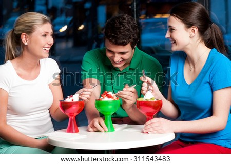 Three friends having deserts in a restaurant - stock photo