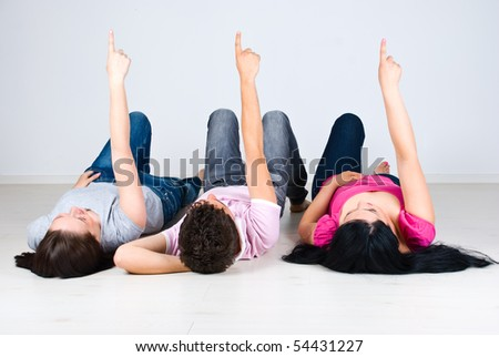 Three friends in a row lying down on wooden floor and pointing up to copy space - stock photo