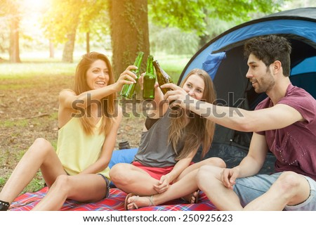 Three friends in camp while celebrating by drinking a beer in a moment of relaxation - stock photo