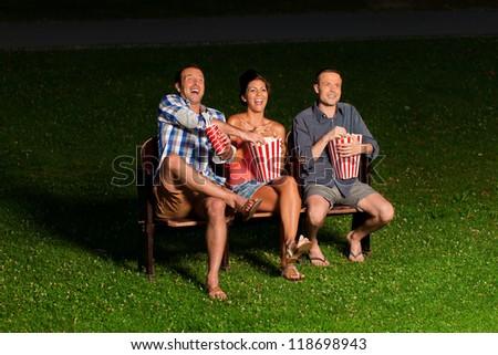 three friends in exterior cinema - stock photo