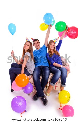 Three friends in hats with balloons sitting on the couch isolated - stock photo