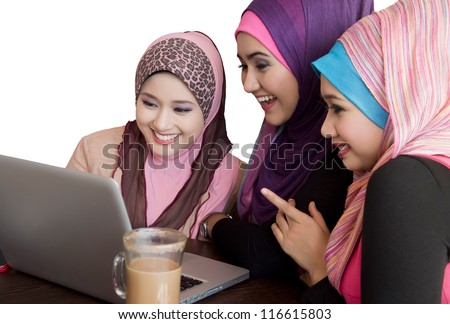 three friends laughing at content on a laptop at cafe - stock photo
