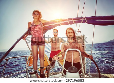 Three friends on sailboat, enjoying summer holidays in the sea, active lifestyle, happy summertime adventure on water transport - stock photo