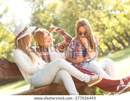 Three friends sitting on a park bench and chatting - stock photo