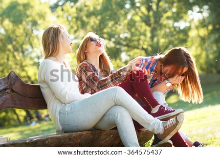 Three friends sitting on a park bench, chatting and enjoying the sunny day - stock photo