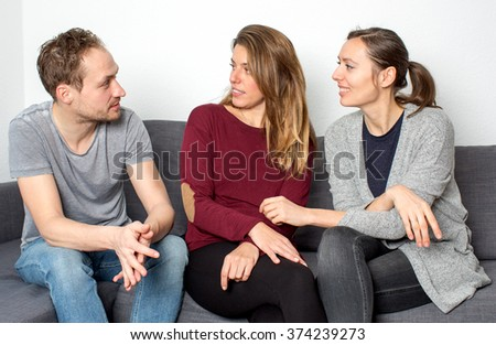Three friends sitting on sofa and talking  - stock photo