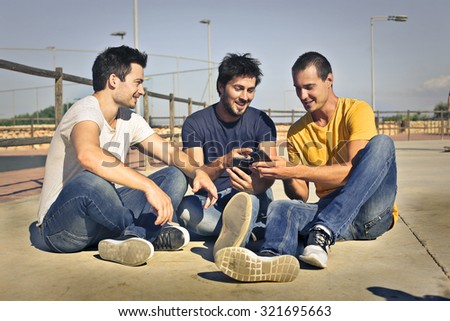 Three friends sitting together - stock photo