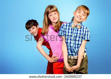 Three friends teenagers standing together. Studio shot. - stock photo