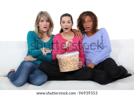 three friends watching television and eating popcorn - stock photo