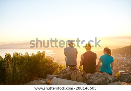 Three friends watching the sunrise over the city together from a mountain nature trail  - stock photo