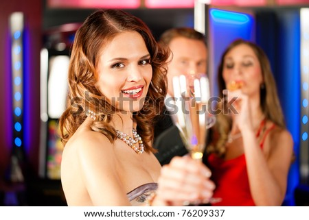 Three friends with champagne in a bar or casino - stock photo