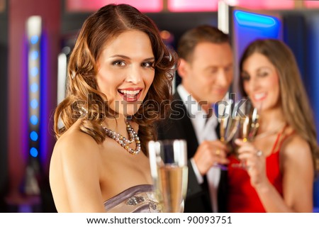 Three friends with champagne in a bar or casino, a woman is looking in the camera - stock photo