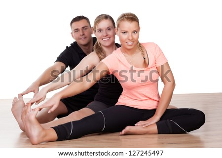 Three friends working out in a gym sitting on the wooden floor doing stretching exercises with their legs extended - stock photo