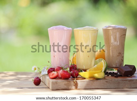 Three fruit or choclate smoothies or milkshakes with fresh organic ingredients including strawberries, cherries, citrus, coffee beans and chocolate blended with yoghurt or icecream - stock photo