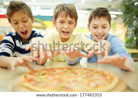 Three funny boys eating pizza in cafe  - stock photo