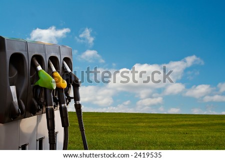 Three gas pump nozzles over a nature background - stock photo