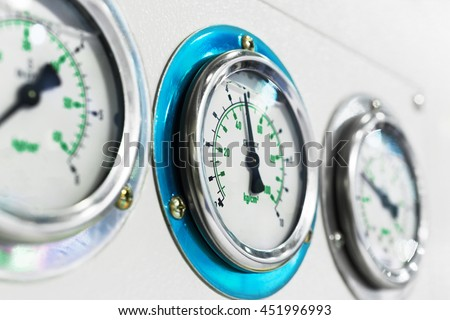 Three gauge on the dashboard of industrial compressor. Shallow depth of field. - stock photo