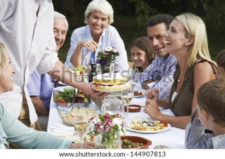 Three generation family celebrating birthday of woman at dining table outdoors - stock photo