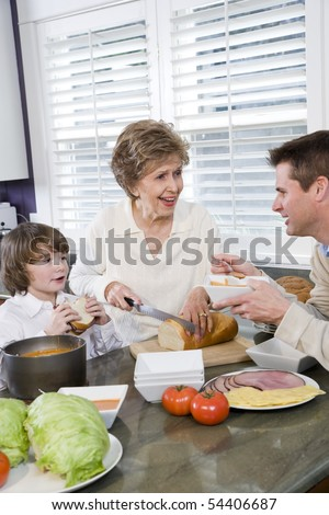 Three generation family in kitchen eating lunch, talking and laughing - stock photo