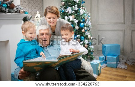 Three generation family reading a book at Christmas Eve at home - stock photo