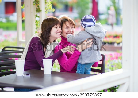Three generations family - grandmother, mother and little son spending time together in an outdoor cafe - stock photo