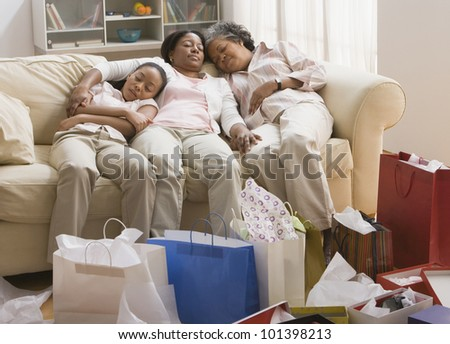 Three generations of African women resting on sofa - stock photo