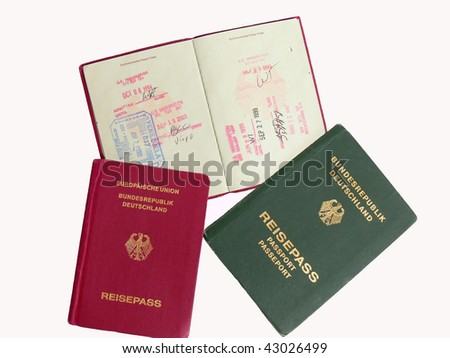 Three German passports, two in red and one old passport in green. There are different stamp of entry in different countries. - stock photo