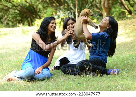 Three Girls are playing with puppy dog - stock photo