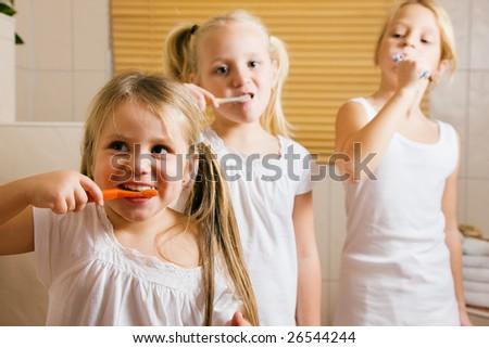Three girls brushing their teeth - stock photo