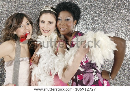 Three girls celebrating with party blowers against a silver glitter background. - stock photo