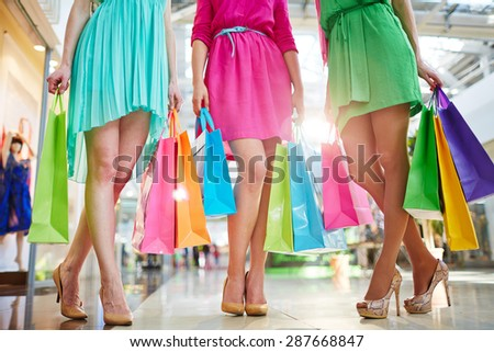 Three girls in bright dresses standing in the mall - stock photo