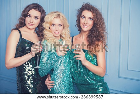 Three girls in evening dresses with champagne glasses - new year, celebration, friends, birthday concept - stock photo