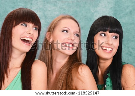 three girls in green dresses on a green background - stock photo