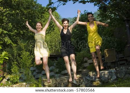 Three girls jumping at the beach, enjoying summertime. - stock photo