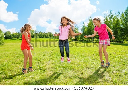 Three girls jumping over the rope in the park, having fun in active games outside - stock photo