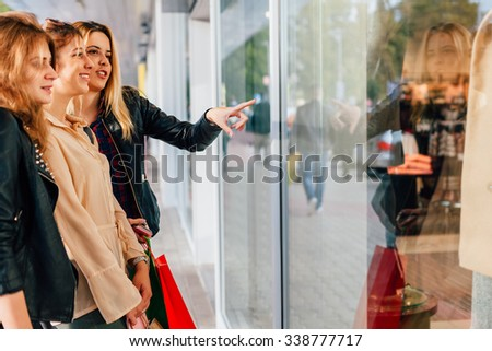 Three girls looking at clothes in a shop window - stock photo