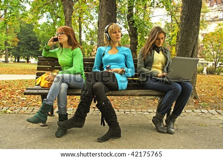 "Three girls on a bench. In ""three different world"" with no friendship. - stock photo"
