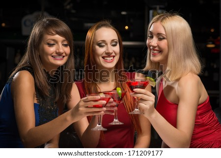 three girls raised their glasses in a nightclub, have fun with friends - stock photo