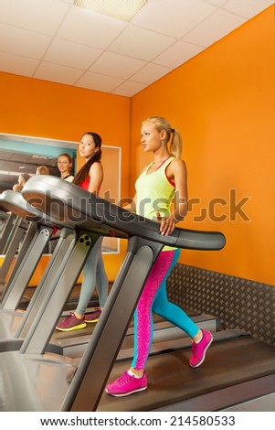 Three girls running in the gym on treadmill  - stock photo