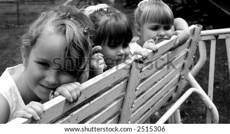Three girls sitting on a wood swing - stock photo